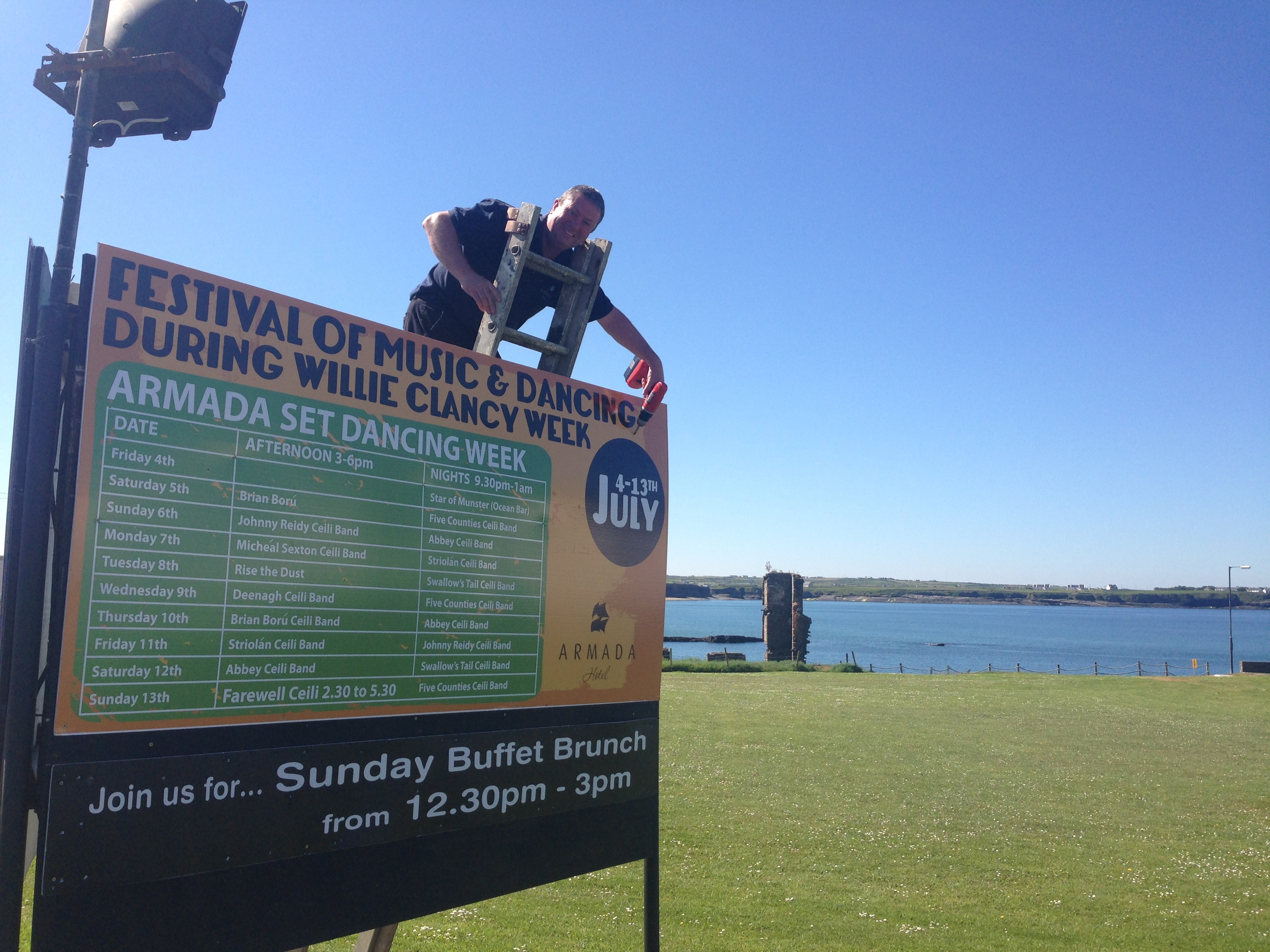 Michael Burke of the Armada Hotel Operations team erects a sign promoting the festival