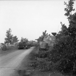 Sherman tanks of the Irish Guards Group advance past others which were knocked out