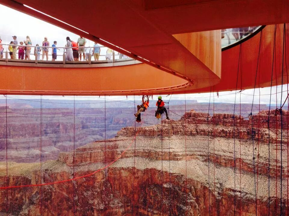 A rope access team cleans the glass walkway at the Grand Caynon