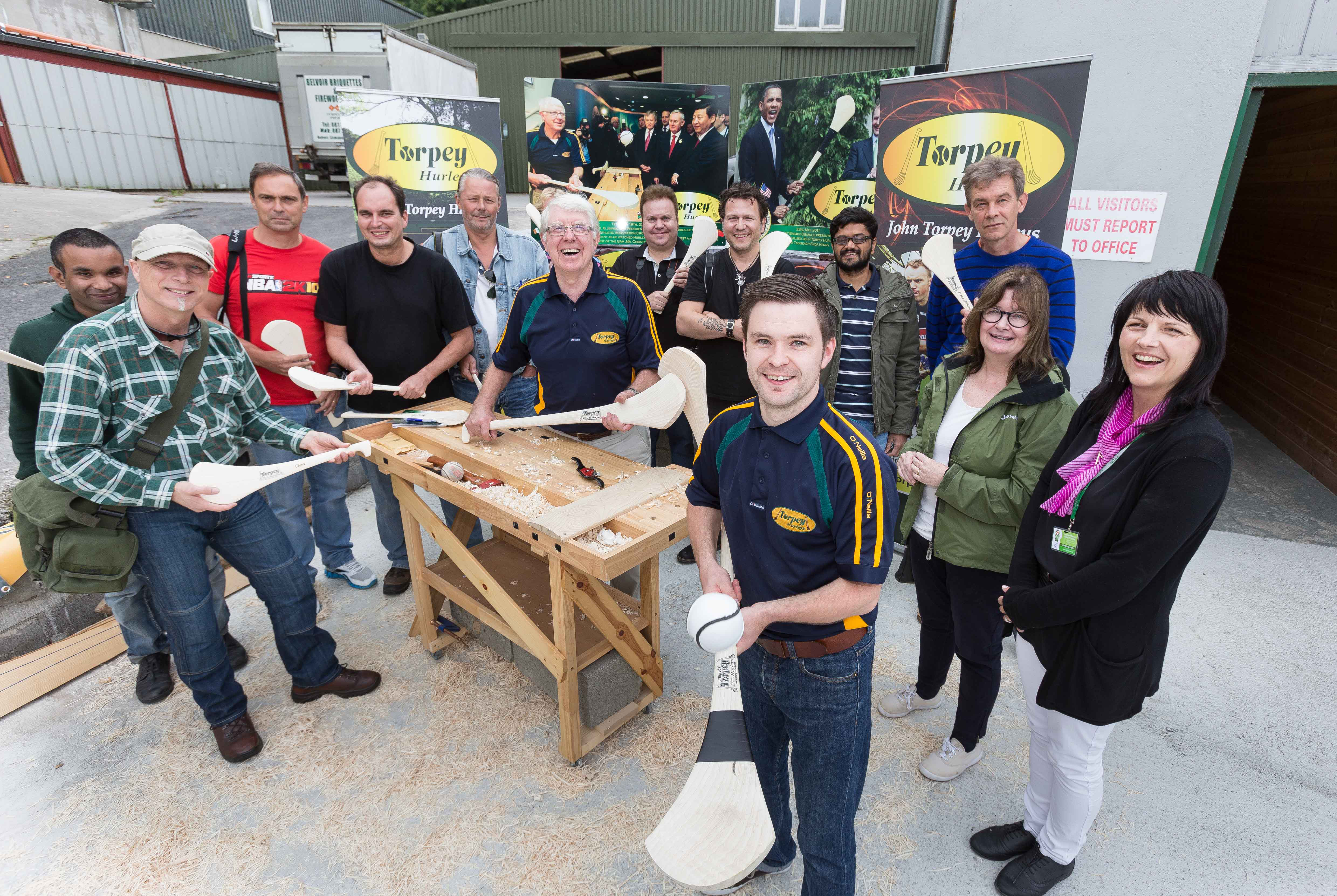 John and Seán Torpey show international travel writers how hurleys are made, at Torpey Hurleys, Sixmilebridge, Co Clare; also pictured are Brenda King, Fáilte Ireland (second right), and tour guide Tanya Jordan (right). Pic – Eamon Ward
