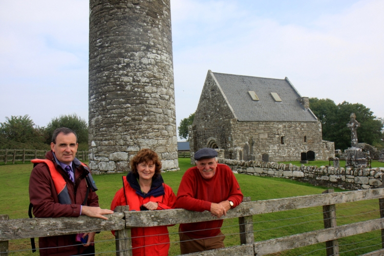 Gerard Dollard, Clare County Council; Dawn Livingstone, CEO, Waterways Ireland; and Ger Madden, Holy Island Tours photographed beside the Round Tower on Holy Island during a visit to the Lough Derg island. Photograph by Gordon Daly
