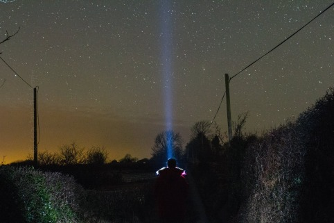 Damien McCarthy holds a torch up against the night sky in Lissycasey, Co. Clare