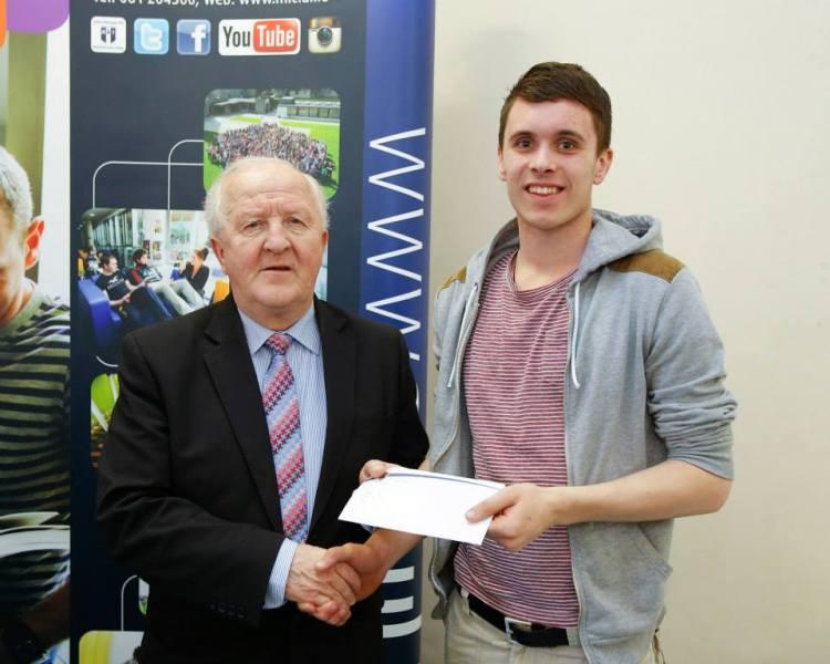 Clonlara's Micheál O'Loughlin receives his bursary from Munster Council Chairman Robert Frost.